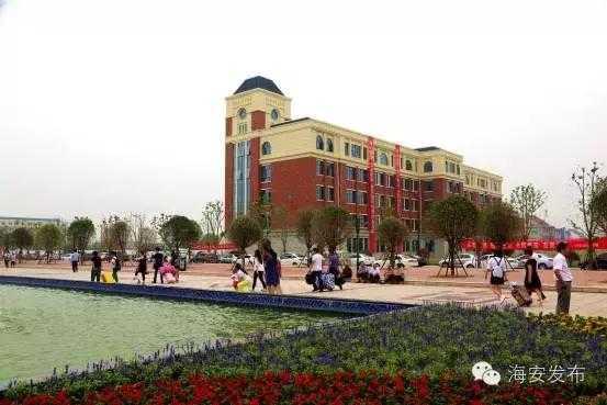 丛花池边,绿树掩映,欧式建筑风格教学楼披着大红条幅静静伫立,在里面