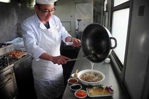 图中是正在火车小厨房里为乘客们做菜的厨师.图片