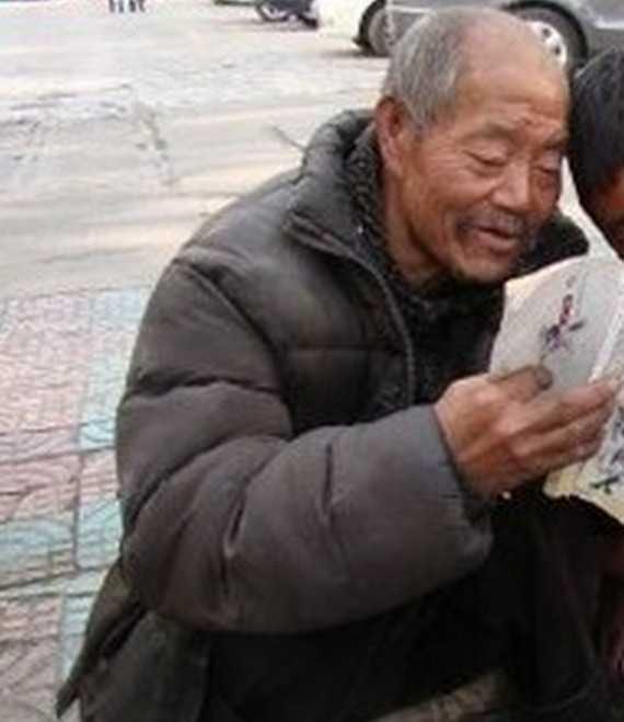 60多岁的乞丐,在街边一边读书 一边乞讨