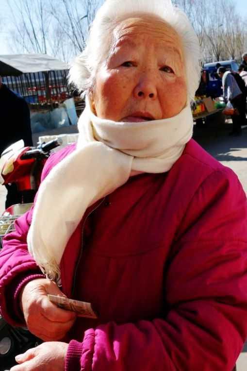 这位白发老奶奶带了2个小朋友来赶集.