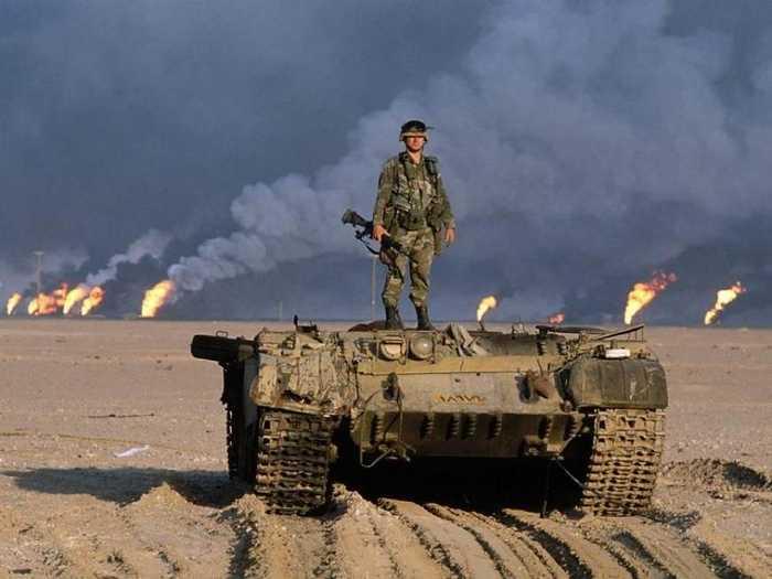一名美军士兵站在一辆炮塔被炸掉的伊拉克坦克上,背景是科威特燃烧的