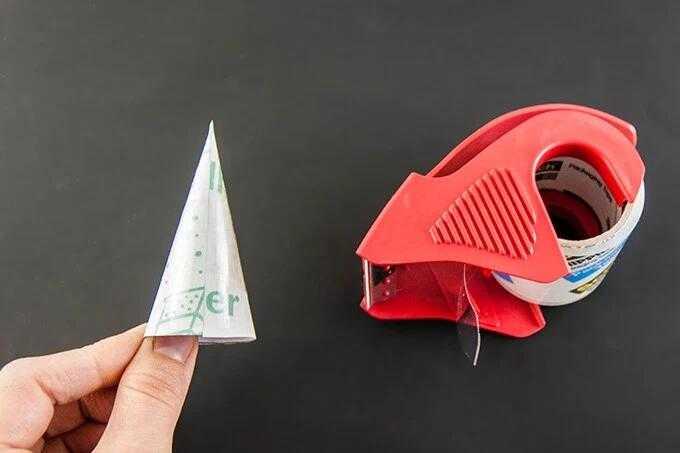 接着,用剪刀在一张纸片上剪出一个扇形的纸片,并将其折成圆锥体用胶带
