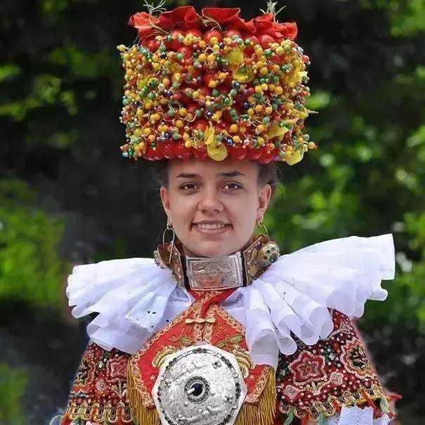 头饰很高,精心装扮了各式珠宝,边际还有鲜花,涵义着婚后日子的富足图片